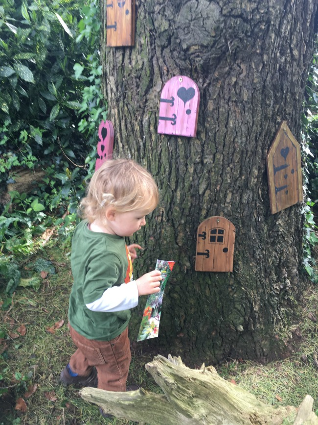toddler by tree covered in fairy doors