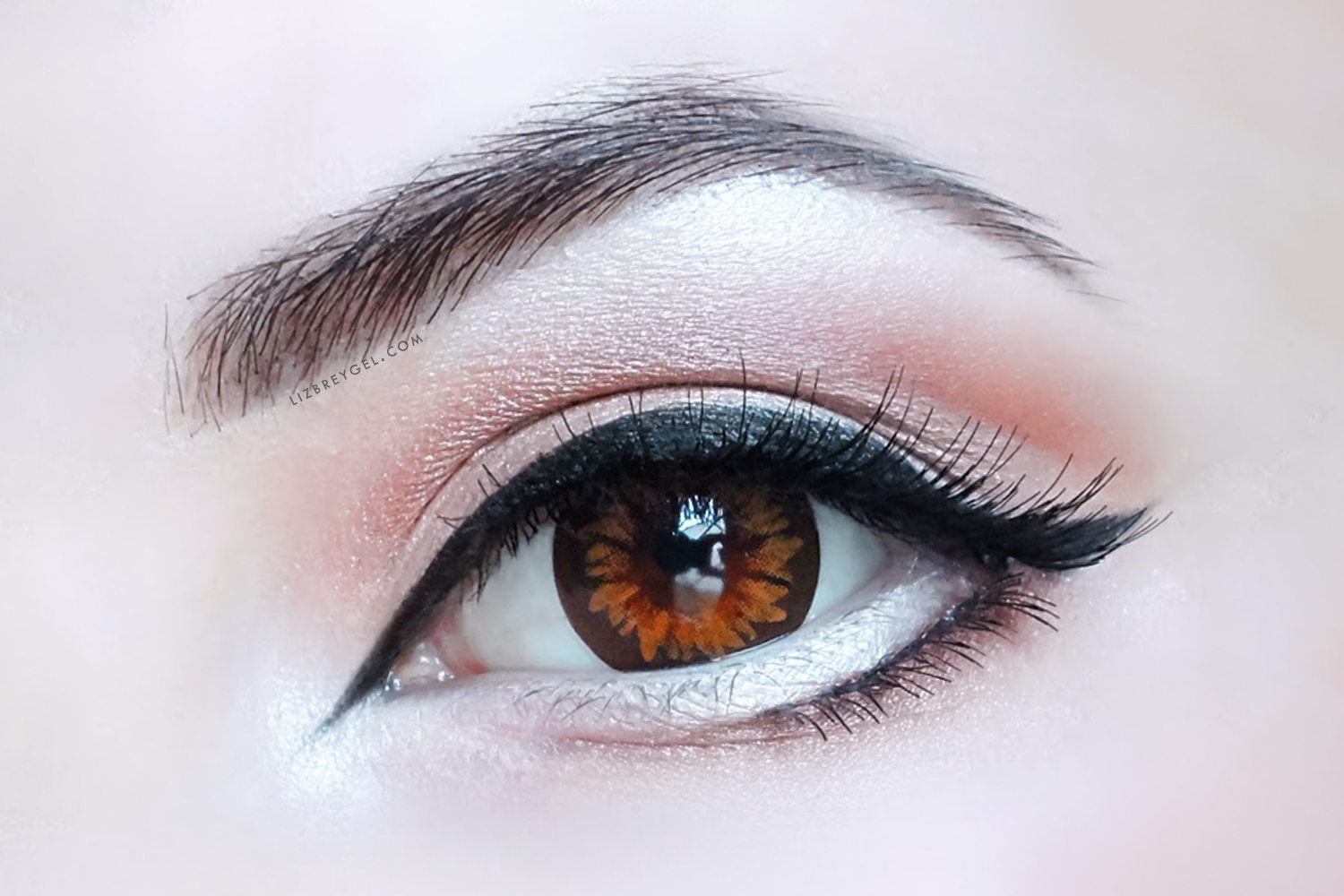 a close up picture of an eye with a special eye-enlarging makeup look and a circle lens