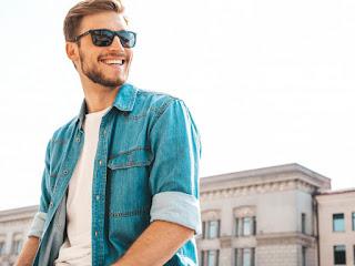 homem jovem usando óculos e camisa jeans sorrindo
