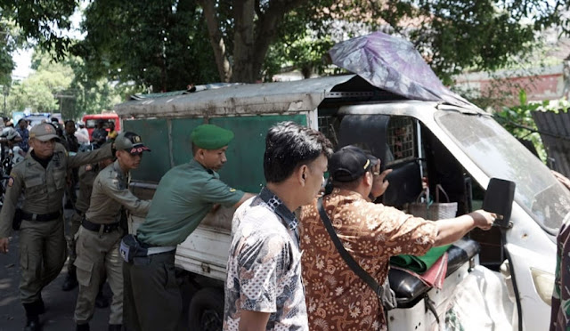 Petugas mengamankan kendaraan yang digunakan untuk berjualan di bahu jalan
