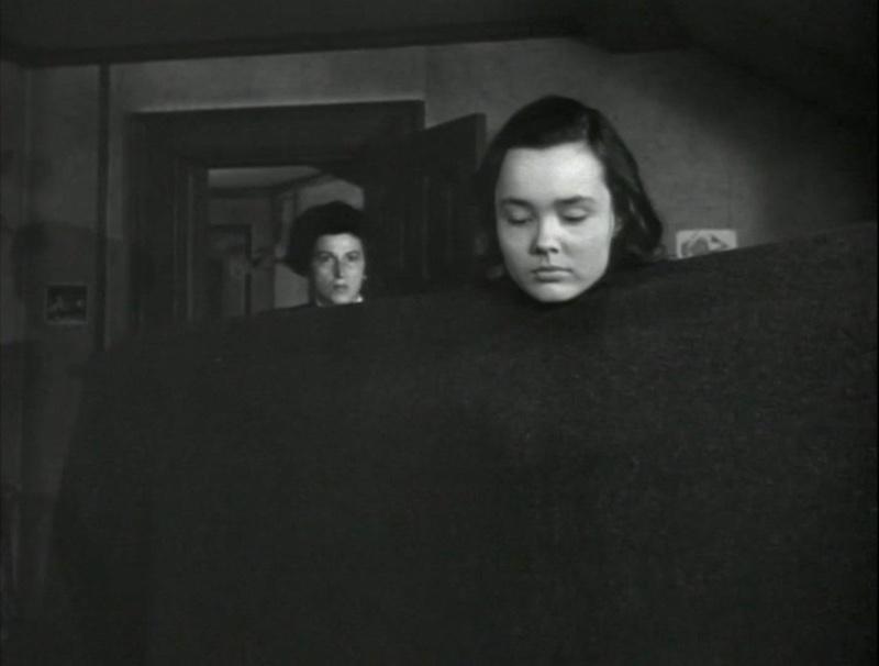 As the blanket lowers, we see Else's head. And Mrs. Melandez is now standing in the doorway behind her.