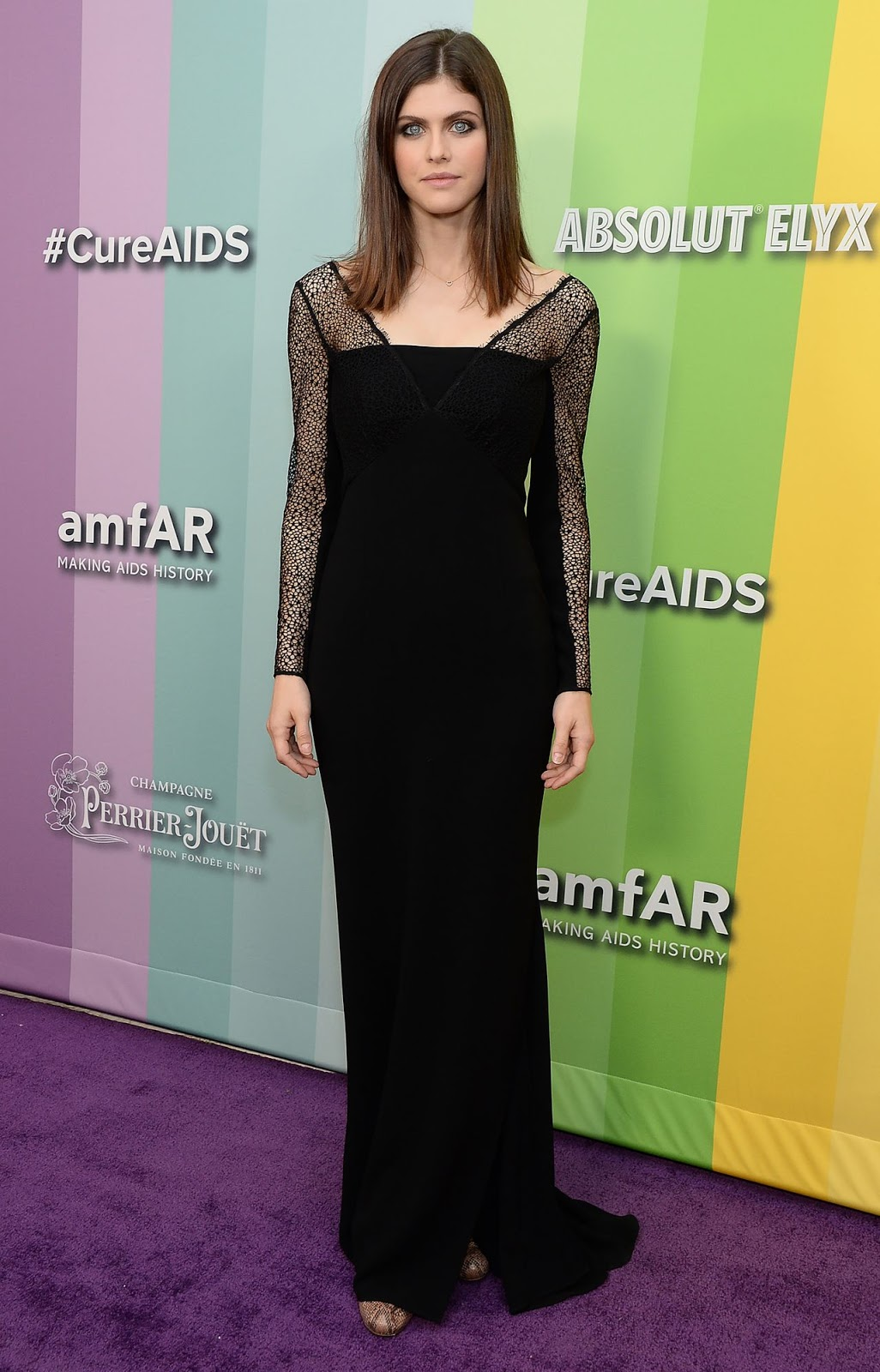 Alexandra Daddario is vampy chic in a black gown featuring webbed mesh sleeves at the 2019 amfAR Inspiration Gala