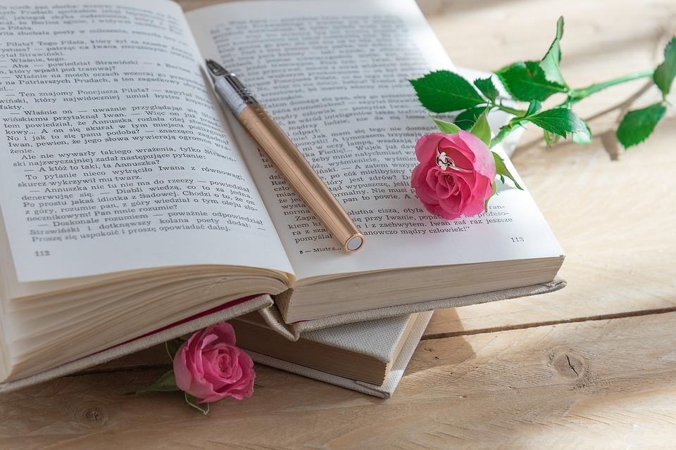 Otwarta książka, na której jest położona róża i pióro.