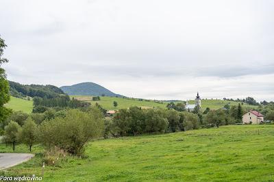 Droga między Izbami a Banicą; z lewej widoczny najwyższy szczyt Beskidu Niskiego - Busov (Słowacja), a z prawej murowana cerkiew w Izbach, obecnie kościół filialny pw. św. Łukasza Ewangelisty