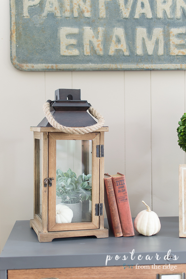 wood and glass lantern with rope handle with vintage books and white pumpkin