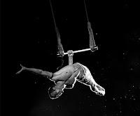Tek eliyle tutunduğu trapezde sallanarak gösteri yapan erkek bir trapezci