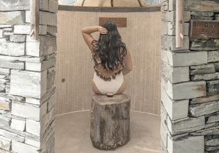 a girl sits inside a stone room, with a little bowl of home made skin scrub.