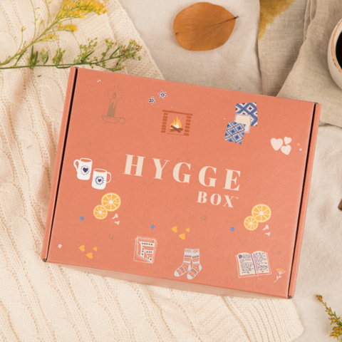 A warm orange box that says Hygge Box on the front with warm and cozy imagery