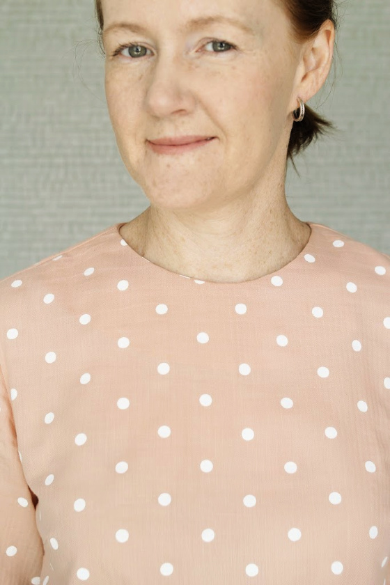 close up photo of a womans face wearing a pink polka dot top