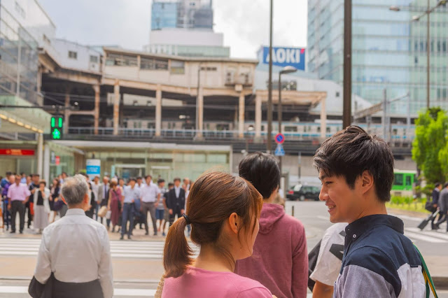 Japanese people including an asian boy and asian girl, locals and tourists crossing a major street in Akihabara, Tokyo Japan