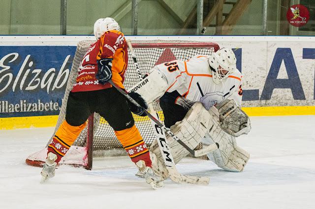 Hokejista raidītā ripa pārlido pāri vārtsarga galvai