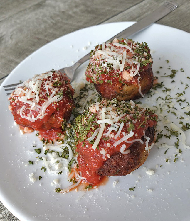 this are three chicken parmesan meatballs with grated cheese and mozzarella on top sitting on a white plate with a fork