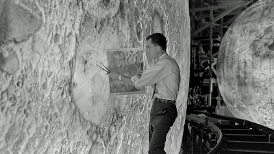 Photo showing a model maker designing a scale replication of the Moon surface.