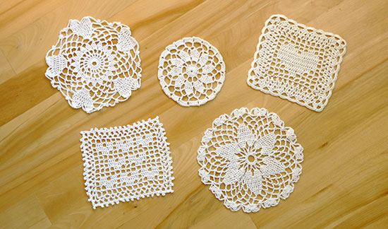 Five white cotton crochet coasters in various heart-inspired designs on a light wood background.