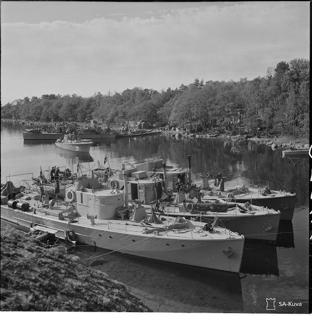 Vanha mustavalkoinen kuva sota-aluksista saaren lahdessa