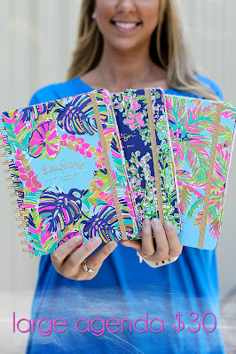 A model holds three Lilly Pulitzer notebooks.