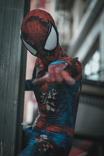 A cosplayer performs the part of Spider-man.