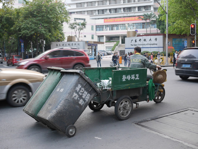 """City Cleaning"" pulling two garbage bins with a three-wheeled motorized vehicle"