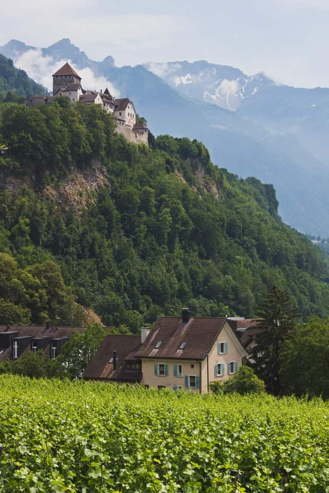 A small cottage surrounded by greens with Vaduz Castle in the background in Liechtenstein