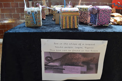 On a table there are several leopard box sculptures with a photo of the original leopard box from the Pitt Rivers