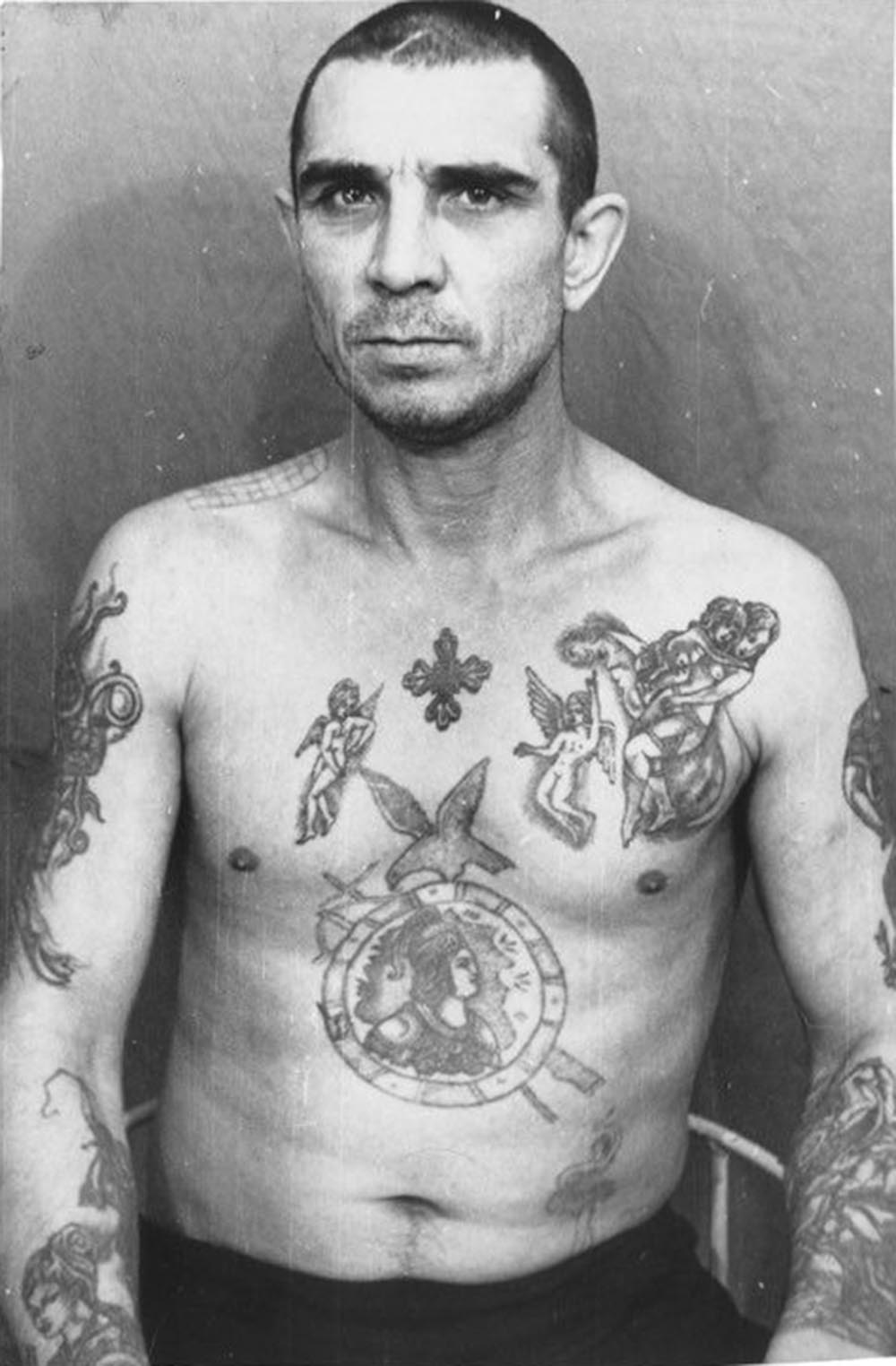 The tattoos on this inmate mimic those of higher ranking criminals. They indicate the bearer has adopted a thief's mentality. However, he does not wear the 'thief's stars;' he is not a 'vor v zakone' or 'thief-in-law,' and therefore holds no real power among this caste.