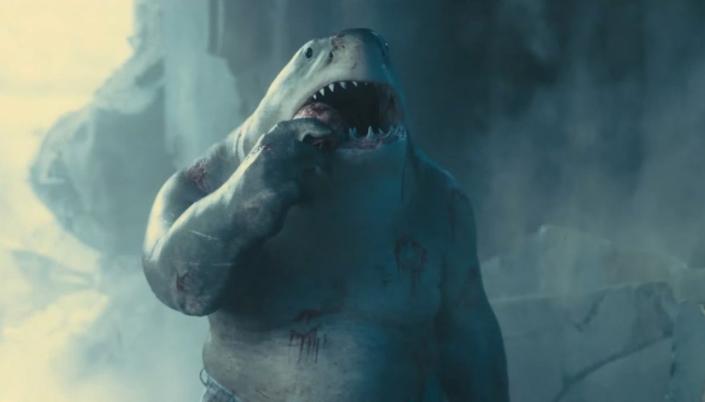 Imagem: cena do filme em que se vê o Rei Tubarão, um humanóide enorme com a cabeça de um tubarão, pequenos olhinhos escuros, o corpo cinzento, mastigando uma coisa, possivelmente um crânio e escombros de uma explosão por trás.