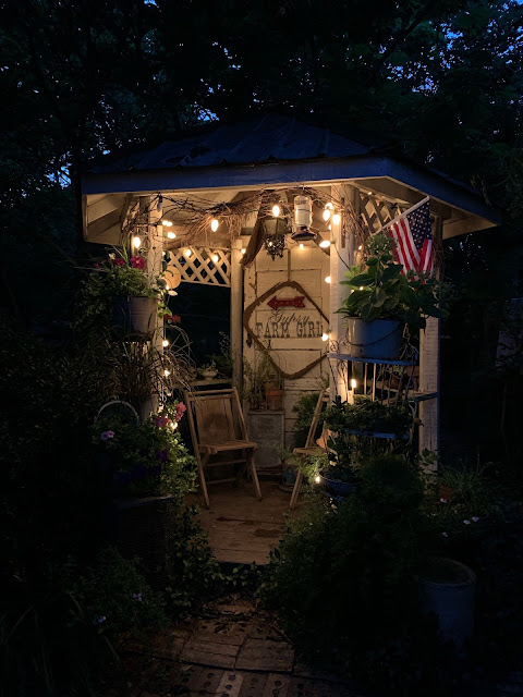 Rustic gazebo at night time with upcycle garden containers and flowers