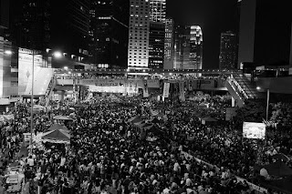 Black and white photograph of a large crowd of people, possibly numbering thousands, some carrying placards, on the streets of a city at night. There are high-rise buildings and neon lights in the background.