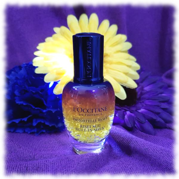 L'Occitane Overnight Reset Oil-In-Serum bottle in front of 3 flowers