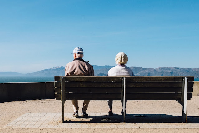 Two old people sat on a bench overlooking a view