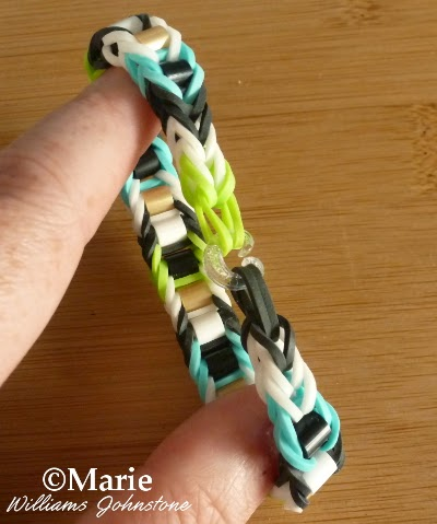Rainbow loom bracelet with bead design in black, white, green and summer blue