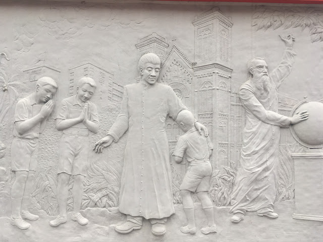 a relief mural along a wall near the cathedral in Bangkok