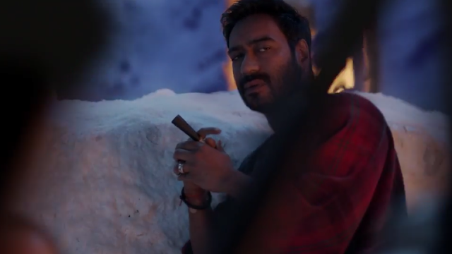 Ajay Devgn in and as Shivaay, Smoking a Cigar