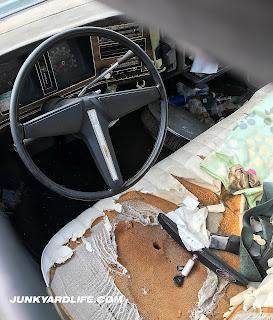 Tri-spoke Pontiac steering wheel in view as we peek through the glass.