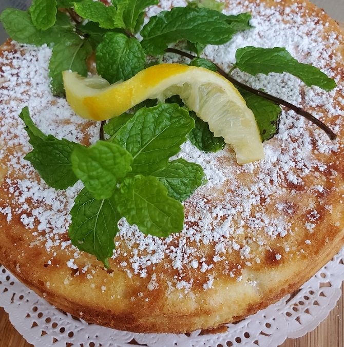 this is a sponge cake dusted with powdered sugar and lemon twist with a sprig of mint on top