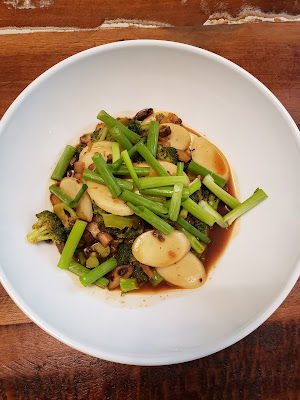a bowl with Korean rice cakes, mushrooms, broccoli, and green onions in a spicy sauce
