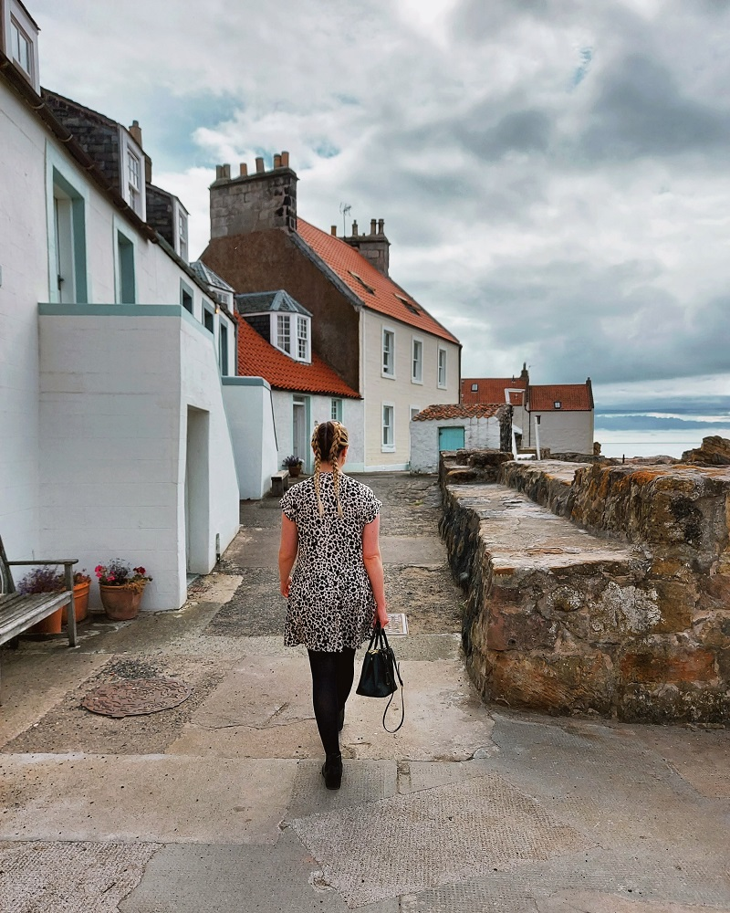 Woman with plaits and leopard print dress walking along the West Shore in Pittenweem