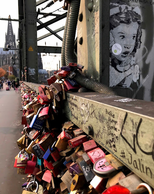 Love-locks in red, blue and silver on a railway bridge decorated with street art of the face of a surprised looking young girl, and in the distance people walking towards a large cathedral.