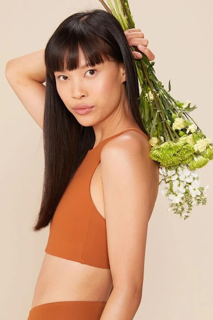 Woman holding flowers and wearing an orange sports bra from Girlfriend Collective