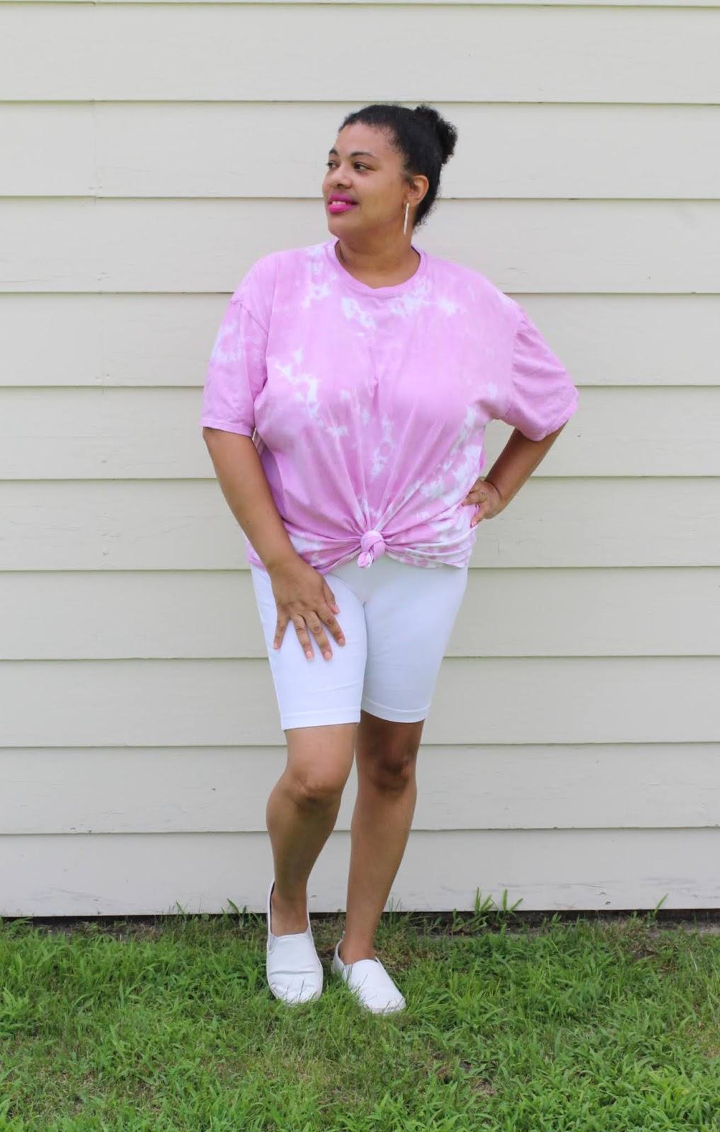 a black woman wearing a pink tie dye shirt with biker shorts