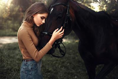 Chica acariciando la cabeza de un caballo en el campo