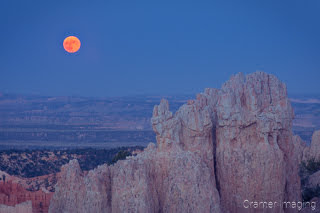 Cramer Imaging's fine art landscape closeup photograph of a red moon rising over a rock formation of Bryce Canyon National Park Utah