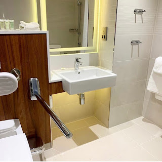 bathroom sink with mirror above and space underneath for wheelchair. Chrome grab rail next to toilet