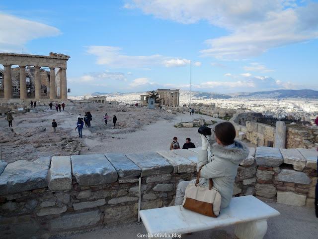 kobieta siedzi na marmurowej ławce trzyma w ręku aparat w oddali turyści przy Partenonie, na niebie białe chmury l
