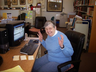 Photo of a library volunteer waving her hands in excitement while sitting at a desk with a computer.