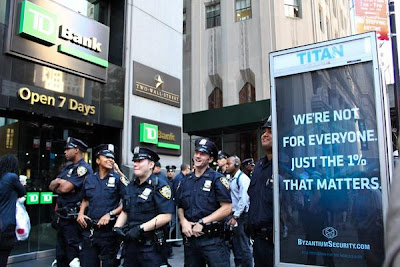 Photo of four unformed cops laughing beside a kiosk poster that reads We're not for everyone, just the 1% that matters