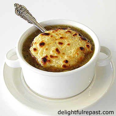 French Onion Soup - and How to Caramelize Onions - Soupe a l'Oignon Gratinee (this photo - soup in two-handled bowl on plate) / www.delightfulrepast.com