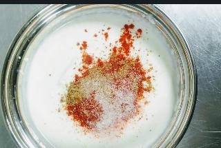 Mixing red chilli powder, salt, pepper in yogurt for chicken 65 recipe