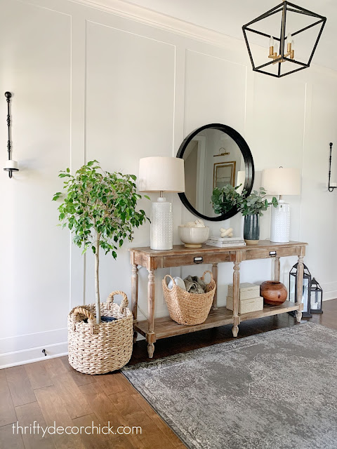 foyer with white wall and trim wood table