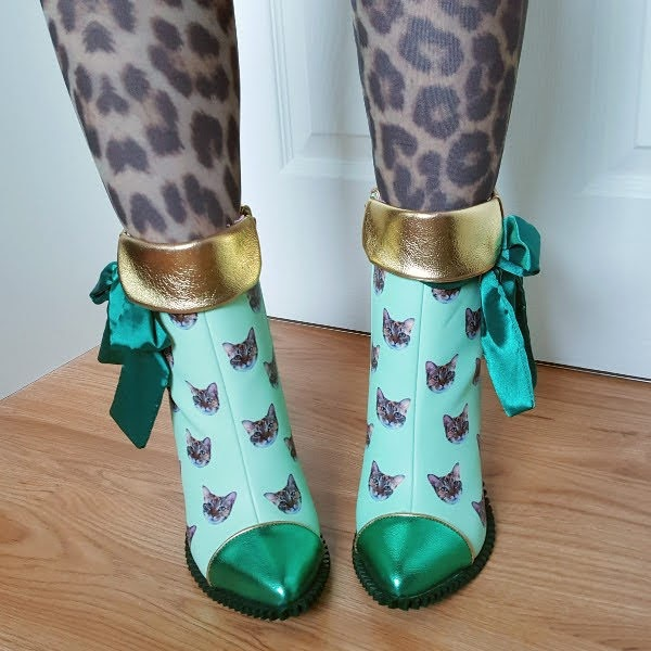 wearing animal print tights and green cat face ankle boots with gold cuffs and satin bows